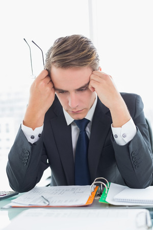 Worried young businessman looking down at documents in office photo