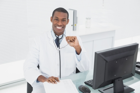 Portrait of a confident smiling male doctor sitting with computer at medical office photo