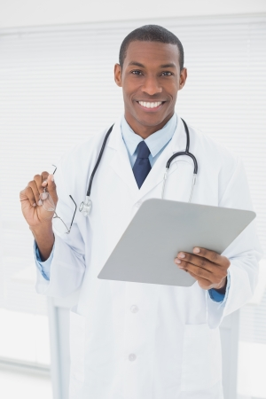 prescribing: Portrait of a smiling male doctor writing a prescription in medical office