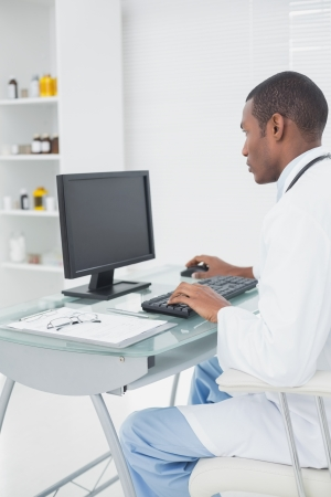 doctor computer: Side view of a concentrated male doctor using computer at medical office Stock Photo