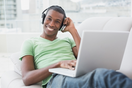 Portrait of a relaxed smiling young Afro man with headphones using laptop on sofa in a bright house photo