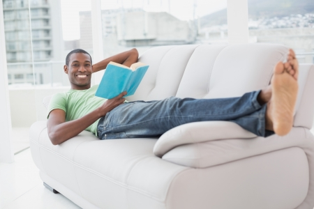 Full length portrait of a smiling young Afro man reading a book on sofa at a bright house photo