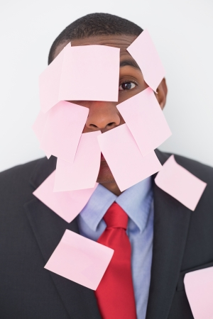 Close up portrait of an Afro businessman covered in blank notes over white background photo