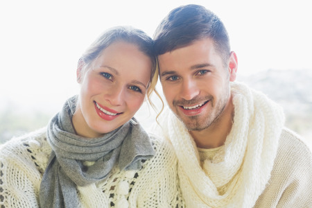 Close up portrait of a loving young couple in winter clothing against bright background photo