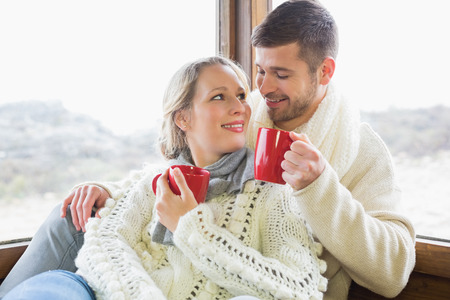 Loving young couple in winter clothing drinking coffee against cabin window photo