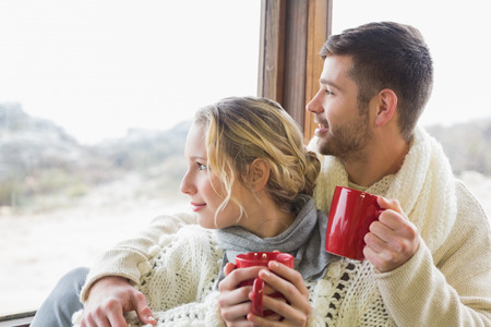 Young couple in winter clothing with coffee cups looking out through cabin window