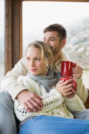 robo: Joven pareja en ropa de invierno con tazas de café mirando a través de la ventana de cabina