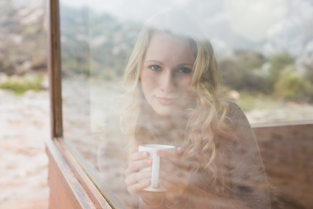 Portrait of a content young woman with coffee cup looking out through cabin window photo