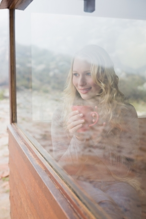 Thoughtful content young woman with coffee cup looking out through cabin window photo