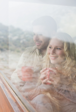 Thoughtful happy young couple with coffee cups looking out through cabin window photo