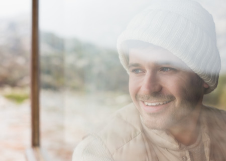 Close up of a thoughtful smiling young man looking out through cabin window photo