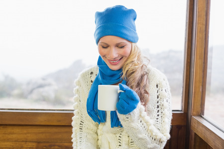 Cute young woman with coffee cup sitting in warm clothing against cabin window photo