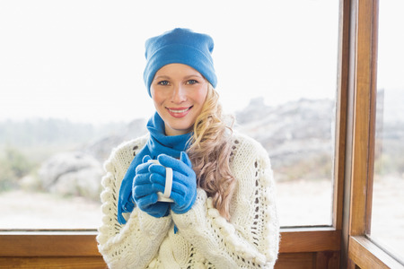 Portrait of a cute young woman with coffee cup in warm clothing against cabin window photo