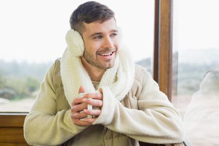 earmuff: Happy young man wearing earmuff with coffee cup against cabin window Stock Photo