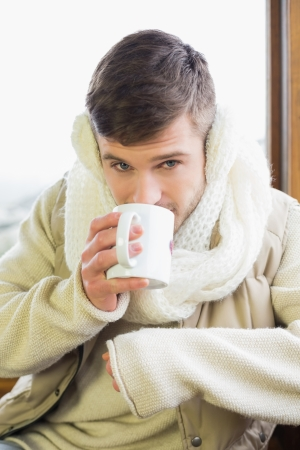 earmuff: Close up of a young man wearing earmuff while drinking coffee against cabin window