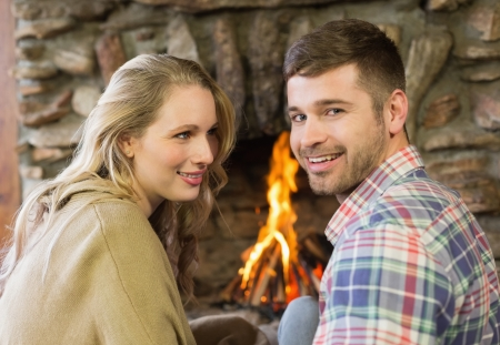 keeping room: Close up portrait of a smiling young couple in front of lit fireplace