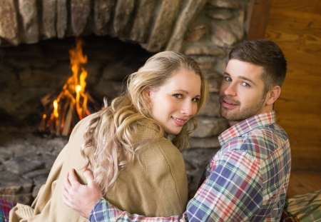 keeping room: Rear view portrait of a romantic young couple in front of lit fireplace Stock Photo