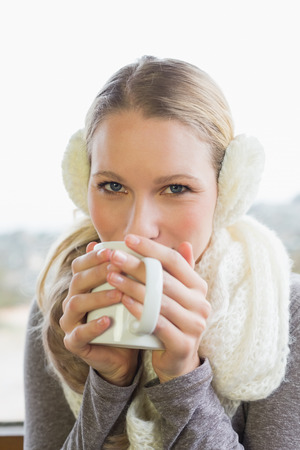 earmuff: Close up portrait of a smiling young woman wearing earmuff while drinking coffee Stock Photo