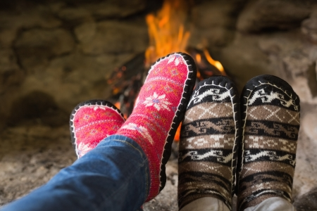 Close up of romantic couples legs in socks in front of fireplace at winter season at home