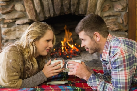 keeping room: Side view of a romantic young couple with tea cups in front of lit fireplace Stock Photo