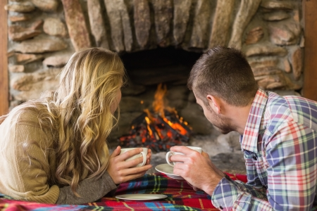 Side view of a relaxed young couple with tea cups looking at lit fireplace photo