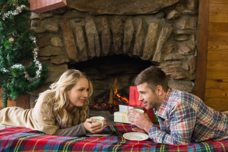 Side view of a young couple with tea cups in front of lit fireplace photo