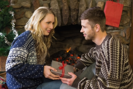 keeping room: Side view of a young man giving Christmas gift box to woman in front of lit fireplace