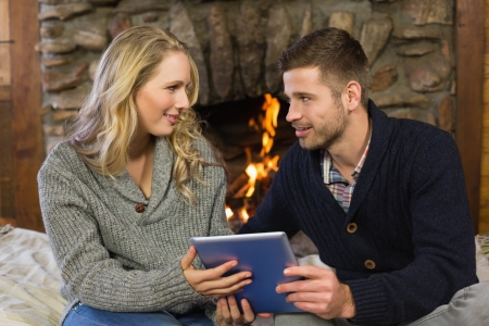 Happy lovely young couple using tablet PC in front of lit fireplace photo