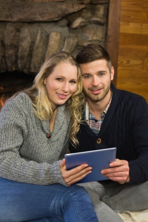 Portrait of a lovely young couple using tablet PC at home photo