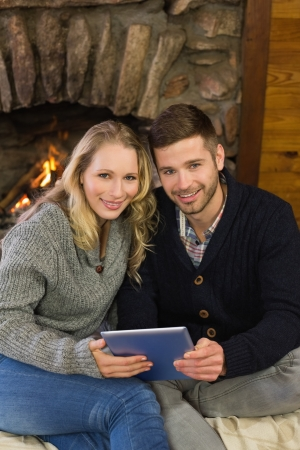 keeping room: Portrait of a lovely young couple using tablet PC in front of lit fireplace Stock Photo