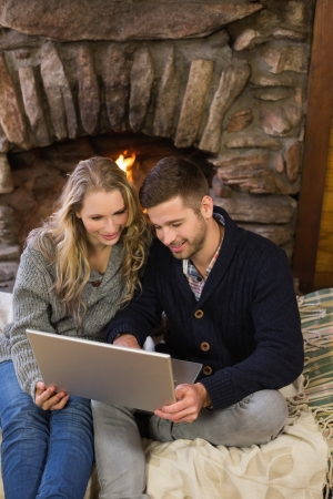 Happy lovely young couple using laptop in front of lit fireplace photo