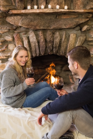 keeping room: Lovely young couple with wineglasses in front of lit fireplace
