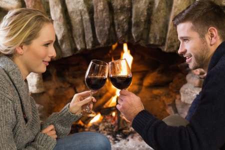 couple lit: Side view of a romantic young couple toasting wineglasses in front of lit fireplace