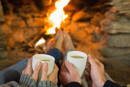 Close up of hands holding coffee cups in front of lit fireplace