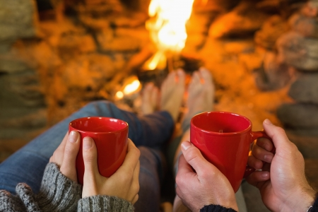 Close up of hands holding red coffee cups in front of lit fireplace Reklamní fotografie