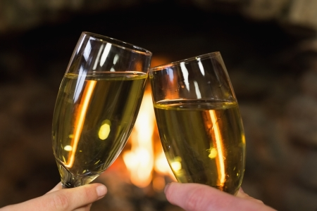 Close up of hands toasting champagne flutes in front of lit fireplace photo