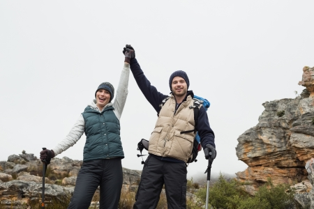 Portrait of a couple standing on rocky landscape with hands raised against clear sky photo