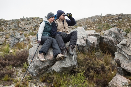 Full length of a young couple sitting on rock with binoculars and trekking pole while on a hike photo