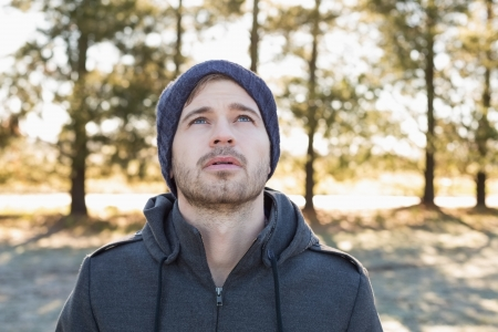 Close up of a young man in warm clothing looking up in forest on a winter day Stock Photo