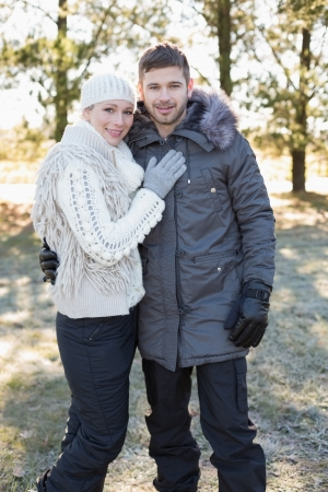 Portrait of a smiling young couple in winter clothing in the woods photo