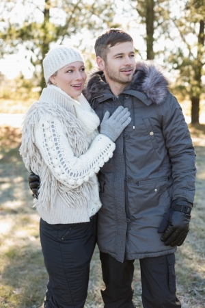 Loving young couple looking away in winter clothing in the woods photo