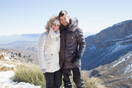 Portrait of a smiling young couple in fur hood jackets against mountain range photo