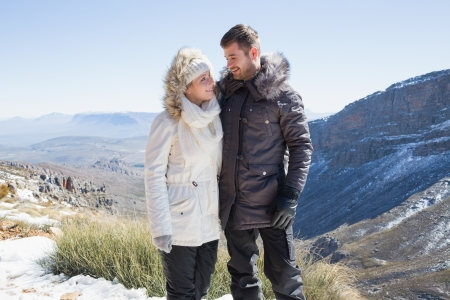 Smiling young couple in fur hood jackets against mountain range photo