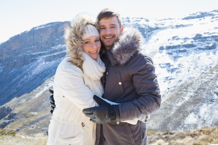 Portrait of a loving young couple in fur hood jackets against snowed mountain range photo