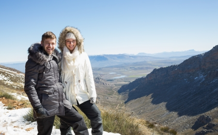Portrait of a loving young couple in fur hood jackets against snowed mountainous valley photo