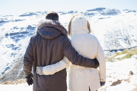 Rear view of a loving couple in jackets looking at snowed mountain range photo