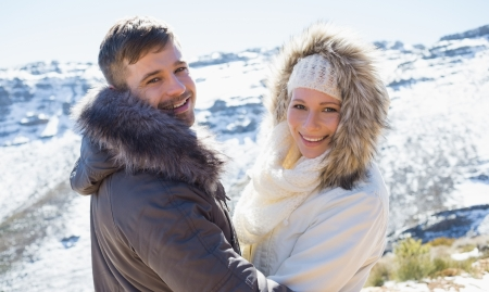 Rear view portrait of a loving couple in jackets in front of snowed mountain range photo