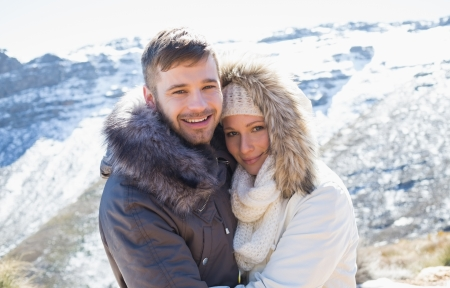 Portrait of a loving couple in jackets embracing in front of snowed mountain range photo