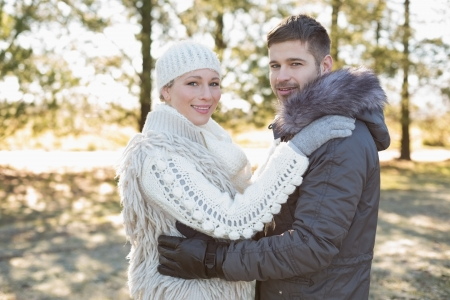 Side view portrait of a loving young couple in winter clothing in the woods photo