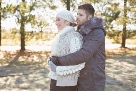 Side view of a loving young couple with arms around in winter clothing in the woods photo